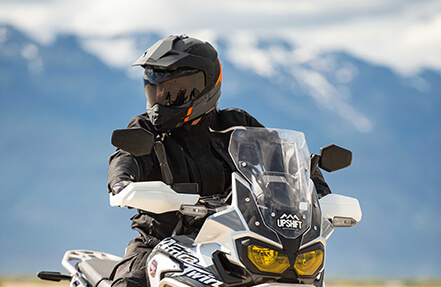 Man riding a grey and black bike wearing a black gmax helmet