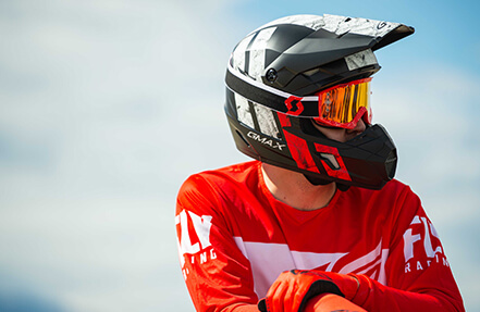 young man wearing a black and red gmax helmet while sitting on his bike